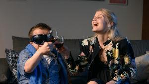 Donna sarjan Alina Tomnikov ja hänen treffikumppaninsa istuvat sohvalla ja kilistävät viinilasejaan nauraen. Lyhytkasvuisella treffikumppanilla on mustat lasit päässään.