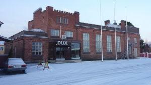 En gammal tegelbyggnad i Kristinestad. Ovanför dörren står dux med stora bokstäver.