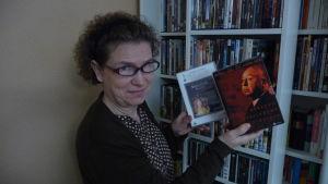 En kvinna visar upp ett par DVD-fodral. Den ena innehåller filmen Shakespeare in love. Den andra tre stycken filmer av Alfred Hitchcock.