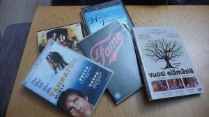 En hög med DVD-filmer ligger på ett bord.
