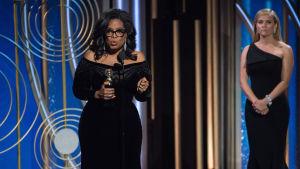 Oprah Winfrey talade om kampen mot sexism och rasism på galan. I bakgrunden står skådespelaren Reese Witherspoon som är en av initiativtagarna till Time's Up.