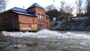 Ett vattenkraftverk i rödtegel, vatten som forsar förbi i en å.