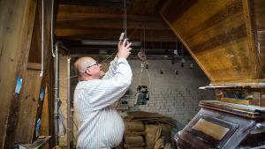 Mies raidallisessa paidassa vanhan myllyn sisällä, nostaa kätensä ylös vetääkseen katosta roikkuvasta narusta.