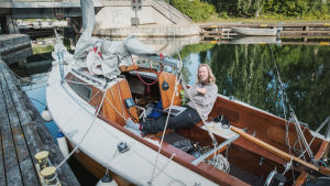 Mies istuu purjeveneessään, joka on kiinnitettynä kanavan laituriin.