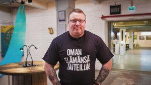 """En man med en t-skjorta som det står """"Oman elämänsä taiteilija"""" på."""