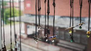 Smycken med fåglar gjorda av glas hänger i ett fönster.