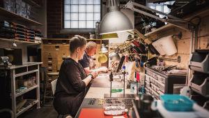 Smyckeskonstnärerna Anniki och Ulf Jensen-Munk sitter vid sina arbetsbord.