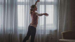Balettdansaren Milja Järvensivu poserar framför ett fönster med gardiner.