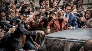 Gail (Michelle Williams) tillsammans med Fletcher Chase (Mark Wahlberg) försöker nå en bil men är omringade av paparazzin.