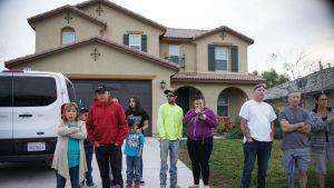 Grannar står utanför familjen Turpins hus i Perris, Kalifornien, där polisen grep föräldraparet och tog om hand syskonskaran på 13 personer.
