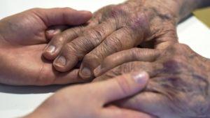 En vårdare håller en äldre persons händer på ett servicehem i Helsingfors 9.8.2016.