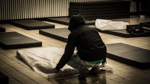 Person med munkjacka och huva bäddar madrasser på golv som nödhärbärge.