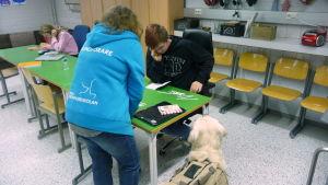 En lärare hjälper en elev. En hund sitter bredvid och tittar på.