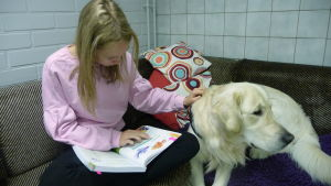 En flicka sitter med en hund i en soffa och läser bok.