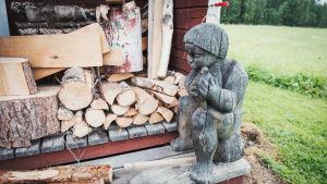 Träskulptur föreställande pojke som sitter på en stubbe, intill en vedtrave.