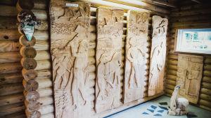 Neljä suorakaiteen muotoista veistotekniikalla tehtyä puutaulua.