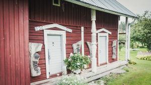 Puuveistoksia lasten profiilikuvista punamullatun ulkorakennuksen seinustalla.