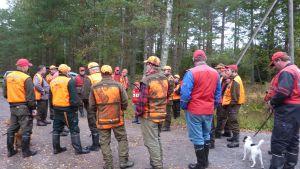 En grupp på cirka 30 personer i orange rockar klara att bege sig ut på älgjakt.