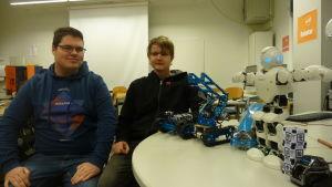 Två manliga studerande sitter bredvid ett bord med robotar uppradade på det.