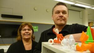 En kvinna och en man står vid olika figurer gjorda med en 3D-printer.