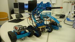 Tre robotar uppradade på ett bord.