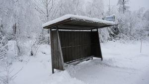 En busshållplats med bruna plåtväggar och plåttak. Mycket snö, i bakgrunden skog.