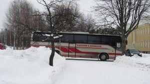 En grå och röd buss åker nerför en snöig gata.