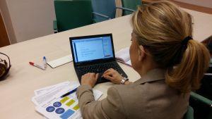 Kvinna skriver på laptop bakifrån.