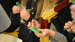 En flicka med Harry Potter- halsduk håller i en rulle med grön tråd.