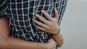 Naisen kädet toisen henkilön ympärillä.
