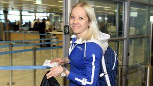 Kaisa Mäkäräinen med en biljett i handen, på väg till Sydkorea