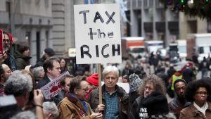 Aktivister demonstrerade mot nya skattelagar utanför börsen i New York medan aktiernas värde rasade