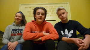 Tre ungdomar sitter på en trappa inne i Kristinestads gymnasium.