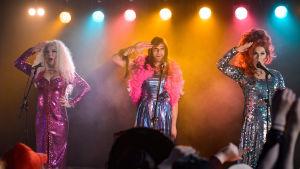 Kolme drag-artistia lavalla käsi lipalla kohti yleisöä. Taustalla värikkäitä valoja ja savua, lavan edessä ihmisiä katsomassa esitystä.