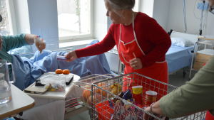 Gunborg Sandström sträcker en chokladstång till en patient.
