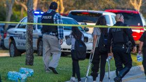 Polis och räddningspersonal assisterar elever utanför skolan i Parkland.