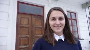 En kvinna med mörkt hår står framför en brun dubbeldörr.