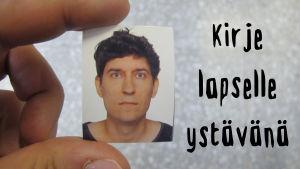 Sormien välissä pidellään Kasper Strömmanin passikuvaa.
