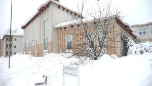 Ett gult hus i snön, skylt där det står Äppelbackens servicehus.