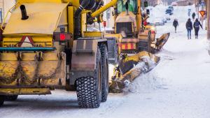 Två vägbjörnar skrapar bort snö och is från en gata.