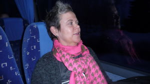 En kvinna med en rosa halsduk sitter i en buss.