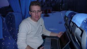 En man med glasögon sitter i en buss med en dator i famnen.
