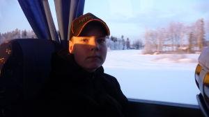 En tonåring med keps på huvudet sitter i en buss.
