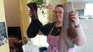 Janna Vehviläinen visar upp två par sockor som donerats till bostadslösa.