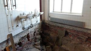 Badrummets lavorarer finns kvar på väggen, men under dem har golvet grävts upp och det medeltida Åbo tittar fram i Katedralskolans gymnastiksal.