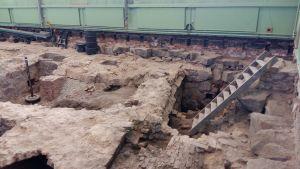 En trappa leder ner till de medeltida arkeologiska utgrävningarna i Katedralskolans i Åbo gymnastiksal.