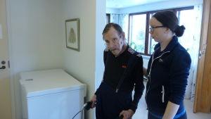 En fysioterapeut hjälper en äldre man att gå med rollator.