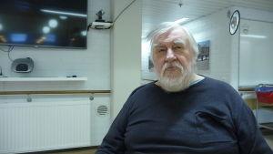 En man med grått hår och skägg sitter i en rullstol.