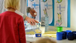 En vuxen person häller upp mjölk åt ett barn på dagis.