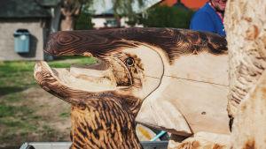 En färdig träskulptur gjord med motorsåg som föreställer en lax.
